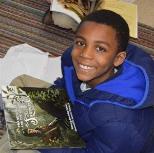 Smiling Marion County student reading a book